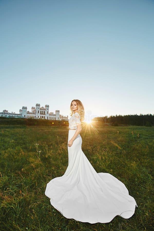 Noiva loura nova, menina modelo bonita com corpo perfeito no vestido branco do laço que levanta com um castelo antigo no foto de stock royalty free