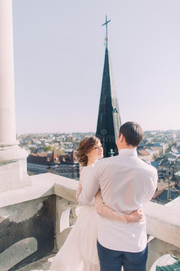 Noiva loura sensual bonita e noivo considerável que abraçam olhando se no balcão do castelo fotografia de stock