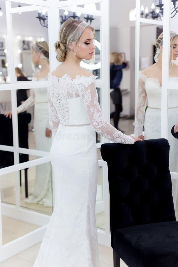 Noiva macia bonito bonita da moça no vestido de casamento nos espelhos com cabelo da noite e composição clara delicada imagem de stock
