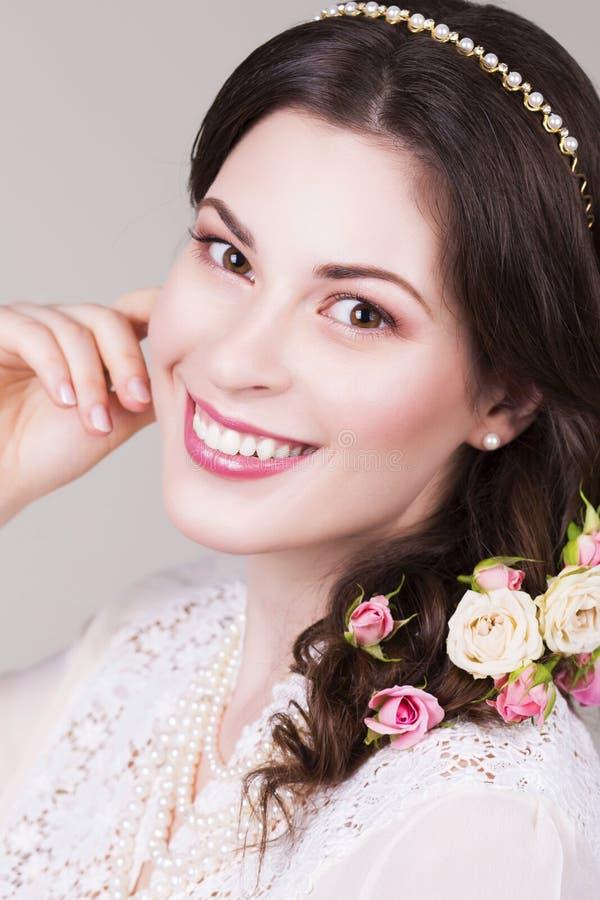 A noiva moreno bonita que sorri com natural compõe e floresce rosas em seu penteado fotos de stock royalty free