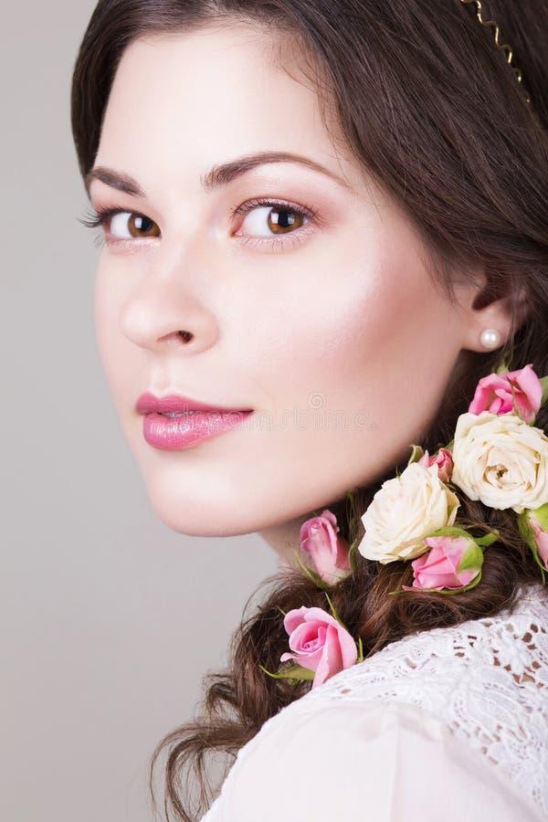 A noiva moreno bonita que sorri com natural compõe e floresce rosas em seu penteado imagem de stock royalty free