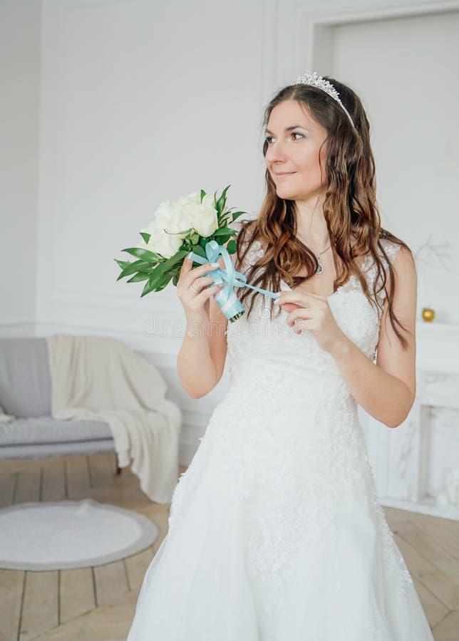 Noiva moreno de sorriso bonita da mulher no vestido de casamento com o ramalhete clássico das rosas brancas imagem de stock royalty free