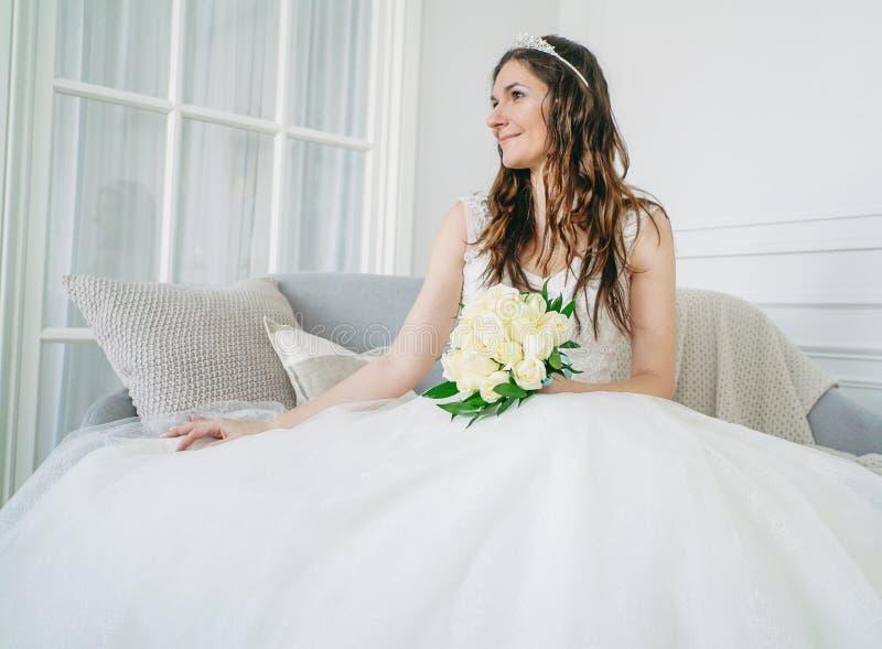 Noiva moreno de sorriso bonita da mulher no vestido de casamento com o ramalhete clássico das rosas brancas na sala de visitas foto de stock royalty free