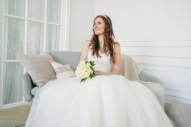 Noiva moreno de sorriso bonita da mulher no vestido de casamento com o ramalhete clássico das rosas brancas na sala de visitas fotos de stock