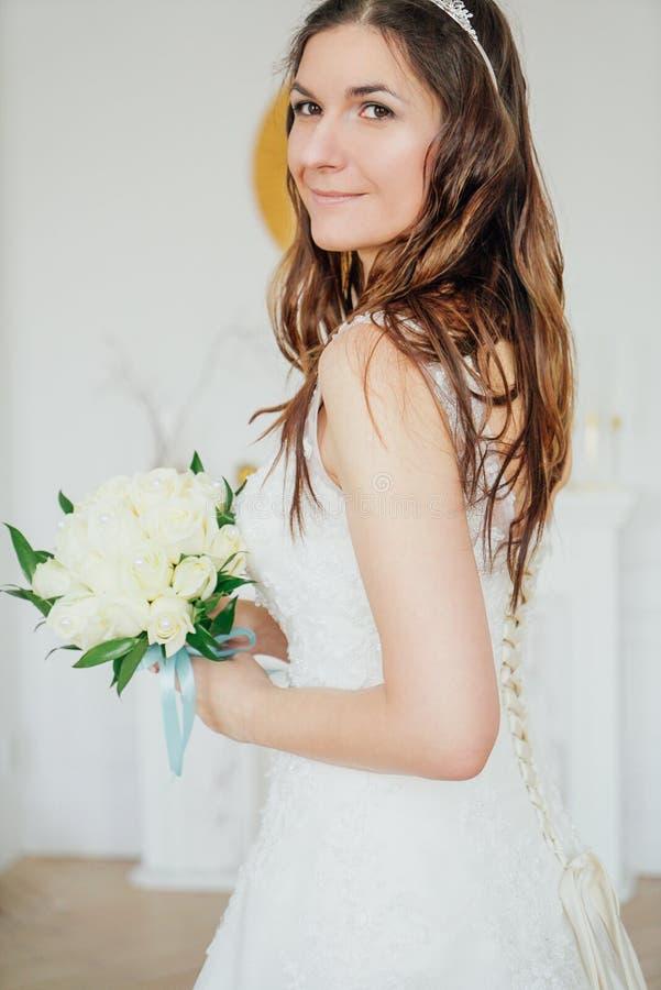 Noiva moreno de sorriso bonita da mulher no vestido de casamento com o ramalhete clássico das rosas brancas na sala de visitas fotografia de stock royalty free