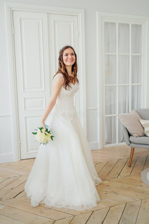 Noiva moreno de sorriso bonita da mulher no vestido de casamento com o ramalhete clássico das rosas brancas, retrato completo do  imagens de stock