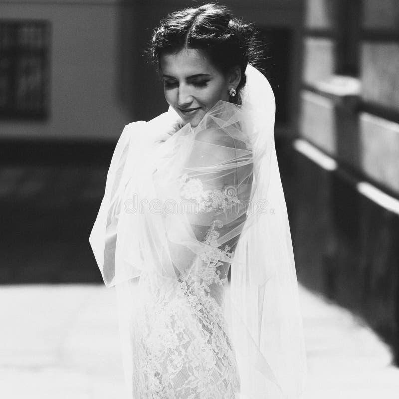 Noiva moreno de sorriso feliz lindo na posição branca do vestido do vintage fotos de stock royalty free