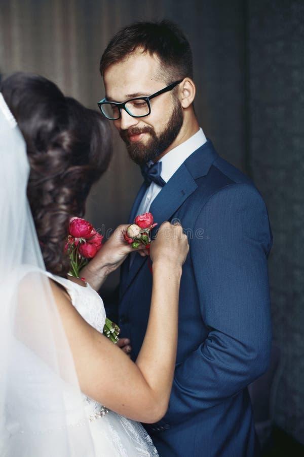 Noiva moreno que põe sobre o boutonniere da flor no noivo feliz em b fotografia de stock royalty free