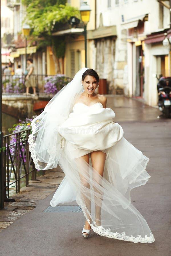 Noiva moreno 'sexy' emocional bonita feliz que mostra os pés no franco foto de stock royalty free