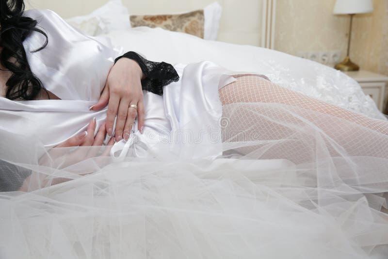 Noiva nas meias brancas e peignoir de seda branco na cama com elementos da seda e do véu Manh? da noiva imagens de stock