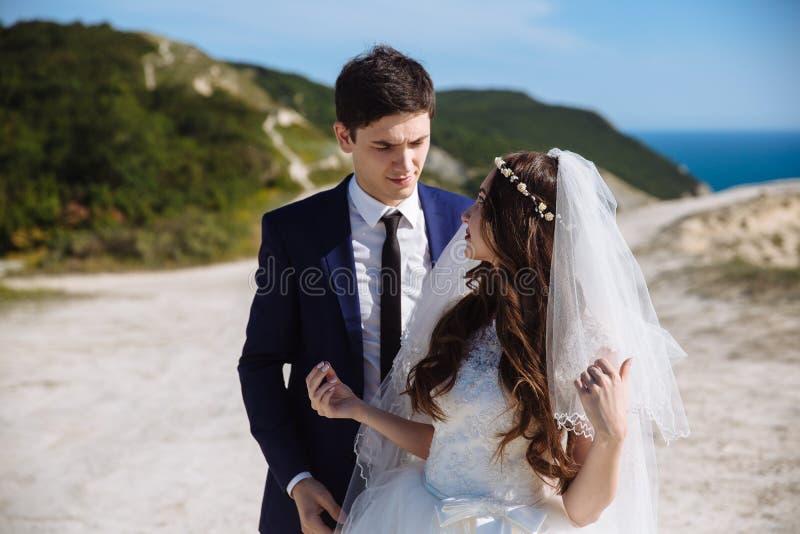 Noiva nas voltas brancas do vestido e do véu para preparar a posição atrás dela fotografia de stock royalty free