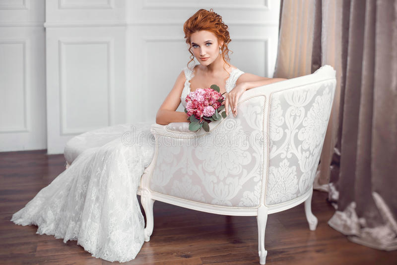 Noiva no descanso de assento do vestido bonito no sofá dentro imagens de stock