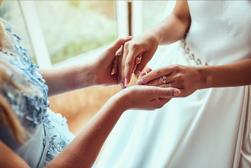 Noiva no dia do casamento que guarda suas mãos do ` s da mãe Conceito do relacionamento entre mamãs e filhas imagem de stock