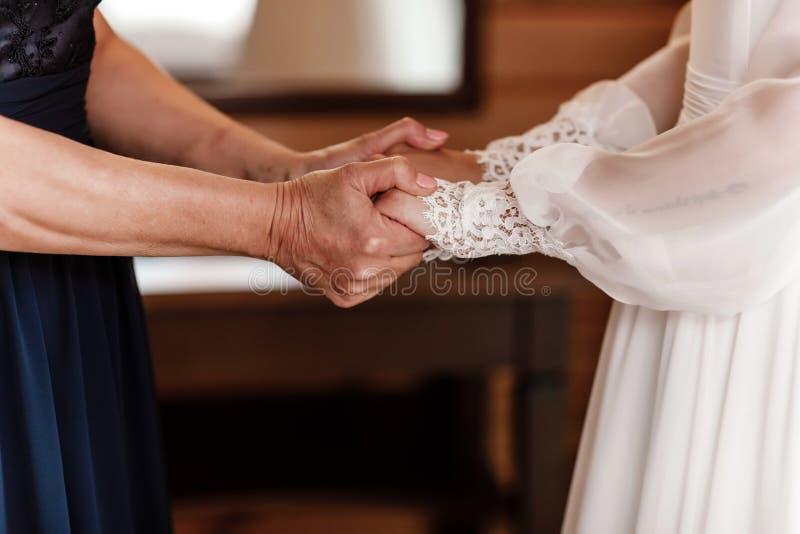 Noiva no dia do casamento que guarda suas m?os do ` s da m?e uma mulher adulta mantém sua filha nova casada imagem de stock