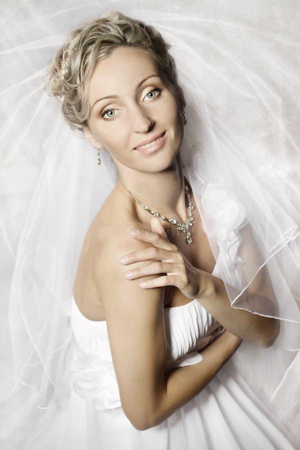 Noiva no véu branco que olha e que sorri na câmera imagem de stock