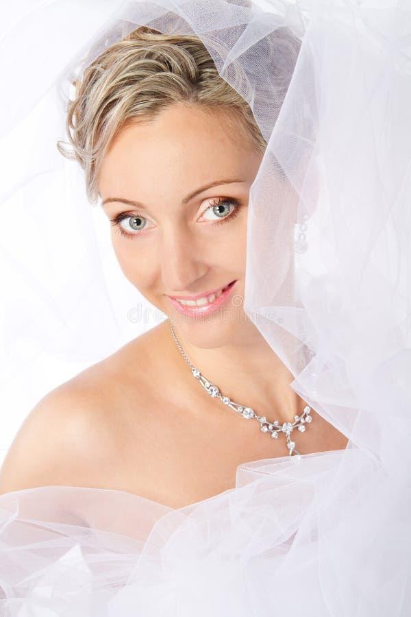 Noiva no véu branco que sorri e que olha a câmera. fotografia de stock