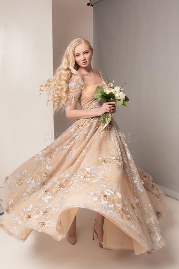 A noiva no vestido bonito que está dentro no interior branco do estúdio gosta em casa Tiro na moda do estilo do casamento novo fotos de stock royalty free