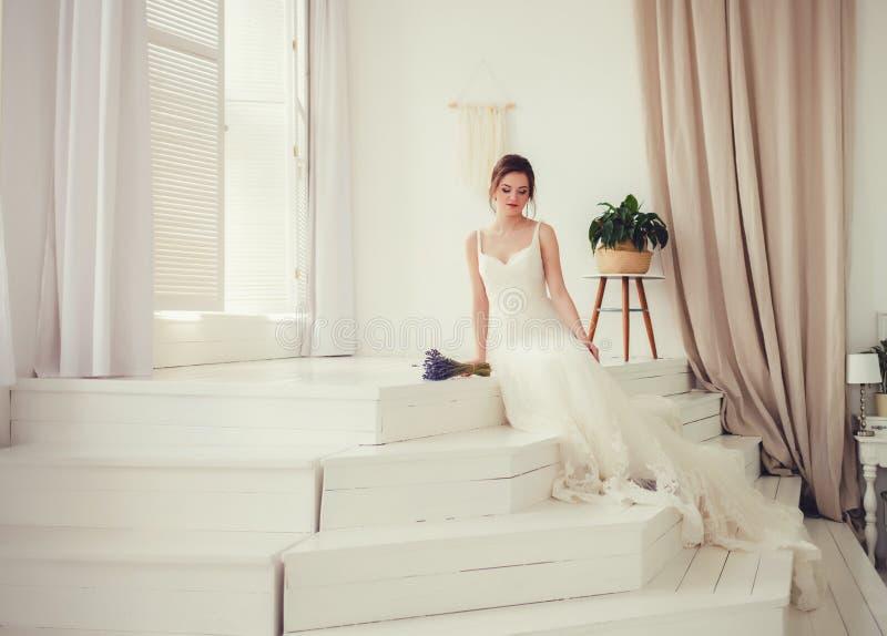 Noiva no vestido bonito que senta-se no sofá dentro foto de stock royalty free