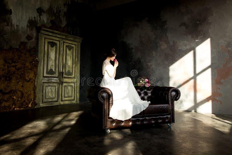 A noiva no vestido branco que senta-se na cadeira dentro no interior escuro do estúdio gosta em casa fotos de stock