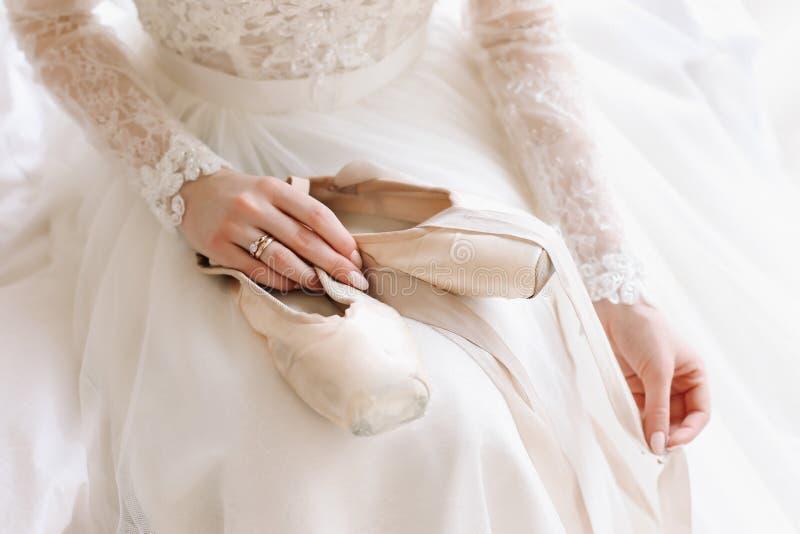Noiva no vestido de casamento clássico elegante com sapatas Manhã da noiva Bailarina com sapatas do pointe fotografia de stock royalty free