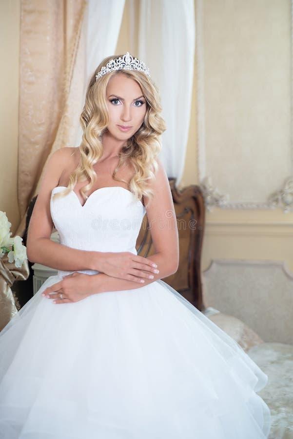 Noiva no vestido de casamento com a coroa no interior Louro imagens de stock