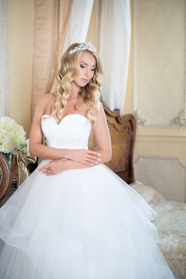Noiva no vestido de casamento com a coroa no interior Louro foto de stock royalty free