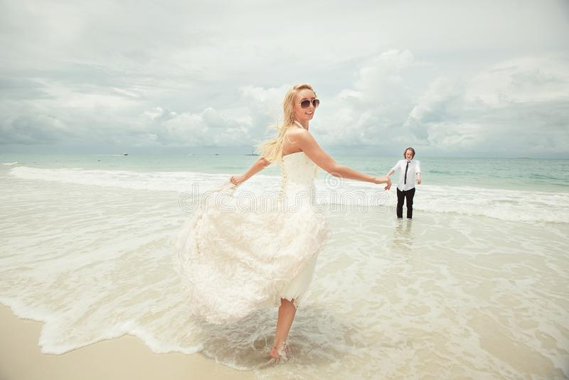 A noiva no vestido de casamento corre ao noivo sobre o mar que gira para trás mulher afortunada na praia fotografia de stock