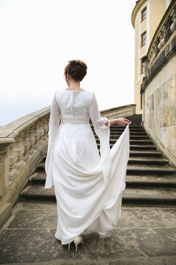 Noiva no vestido de casamento em escadas do castelo no dia nebuloso fotos de stock