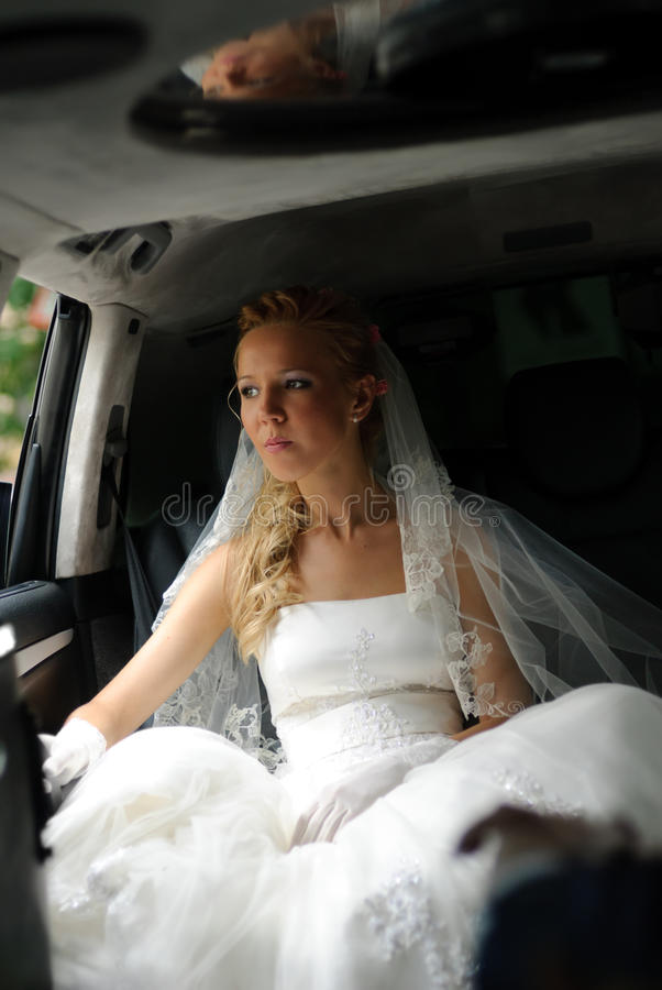 A noiva no vestido de casamento senta-se na limusina imagem de stock royalty free