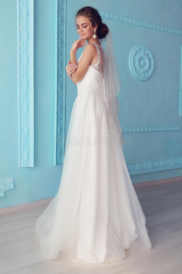 Noiva nova bonita com cabelo encaracolado escuro no vestido de casamento luxuoso que levanta na sala fotos de stock