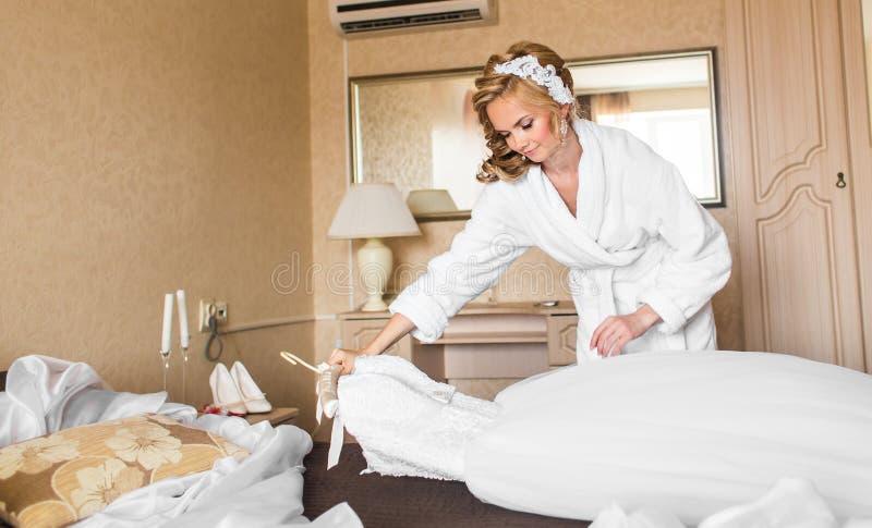 A noiva nova bonita com composição do casamento e o penteado no quarto, mulher atrativa do recém-casado têm a preparação final pa foto de stock