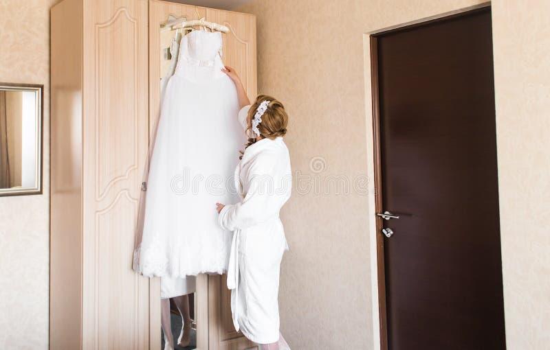 A noiva nova bonita com composição do casamento e o penteado no quarto, mulher atrativa do recém-casado têm a preparação final pa fotografia de stock