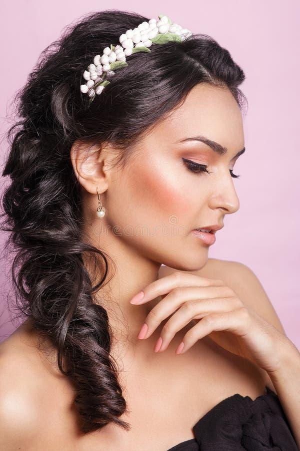 Noiva nova bonita com um ornamento floral em seu cabelo Mulher bonita que toca em sua face Conceito da juventude e dos cuidados c foto de stock