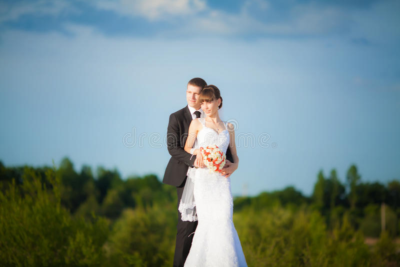 Noiva nova bonita feliz com o noivo na natureza do verão do amor para fora imagem de stock royalty free