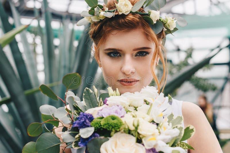 noiva nova bonita na grinalda floral que guarda o ramalhete e a vista do casamento imagens de stock