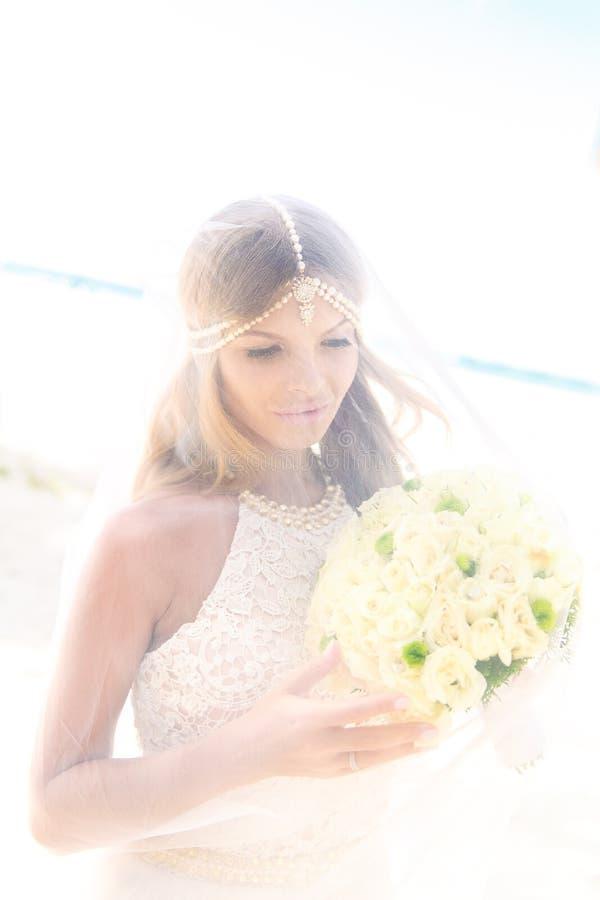 Noiva nova bonita no véu, com o ramalhete do casamento do branco imagem de stock royalty free