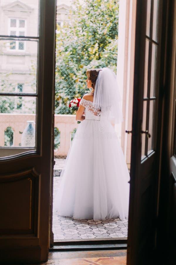Noiva nova bonita no vestido de casamento que guarda um ramalhete bonito que está no balcão da construção do vintage foto de stock