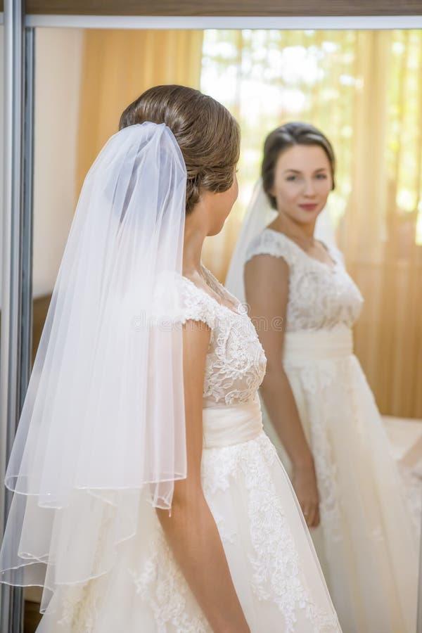 Noiva nova bonita no vestido de casamento que olha no espelho fotos de stock