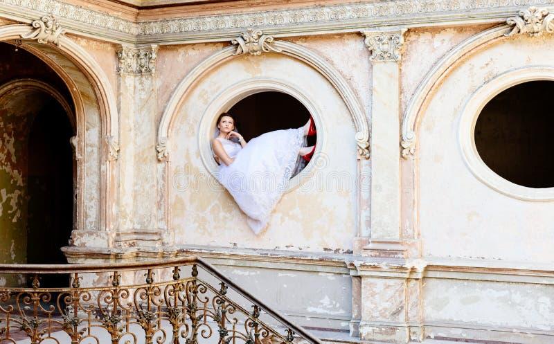 Noiva nova bonita que levanta na janela foto de stock
