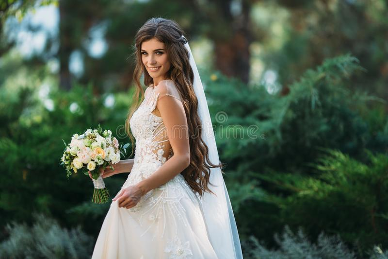 A noiva nova bonito com os cabelos longos que guardam seu ramalhete do casamento inclui as rosas brancas e as outras flores Branc fotos de stock royalty free