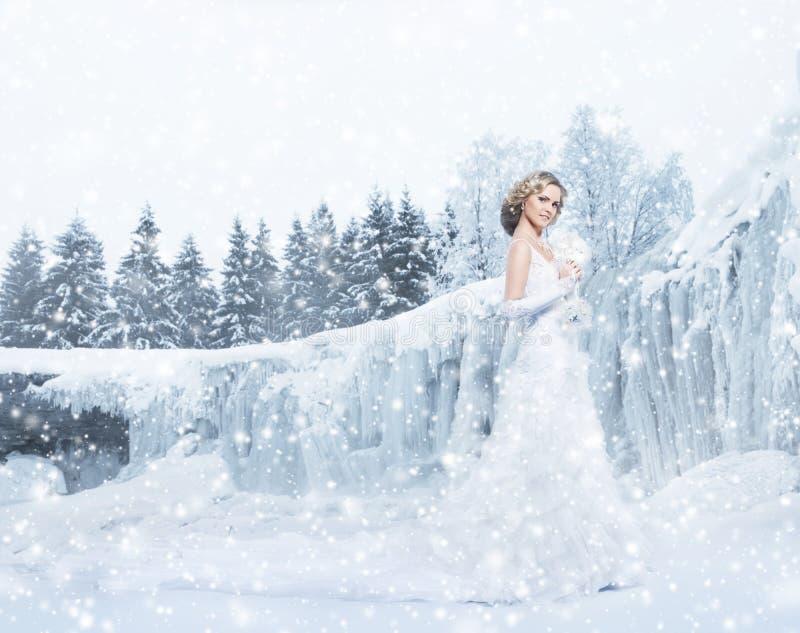 Noiva nova e bonita que levanta em um fundo nevado do inverno fotografia de stock royalty free