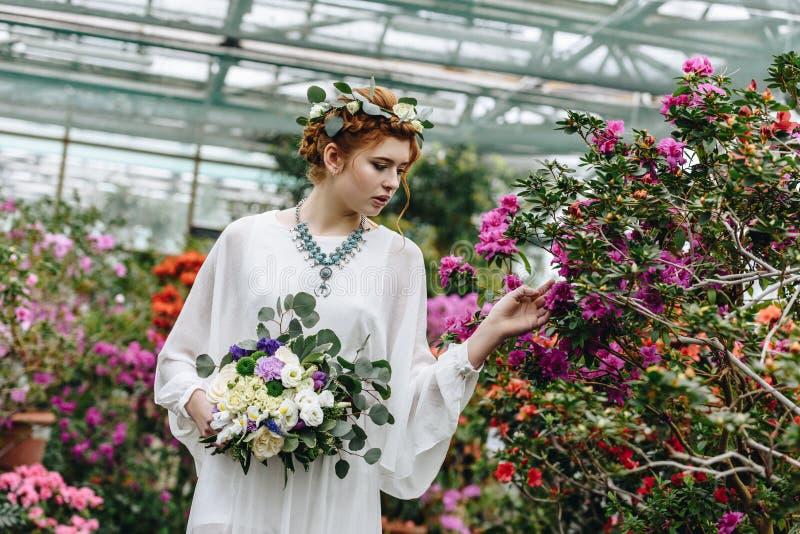 noiva nova elegante bonita que guarda o ramalhete do casamento e que toca em flores fotos de stock royalty free