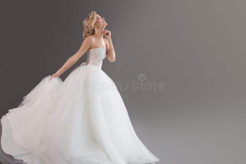 Noiva nova encantador no vestido de casamento luxuoso Menina bonita no branco Emoções da felicidade, do riso e do sorriso, cinzen foto de stock royalty free
