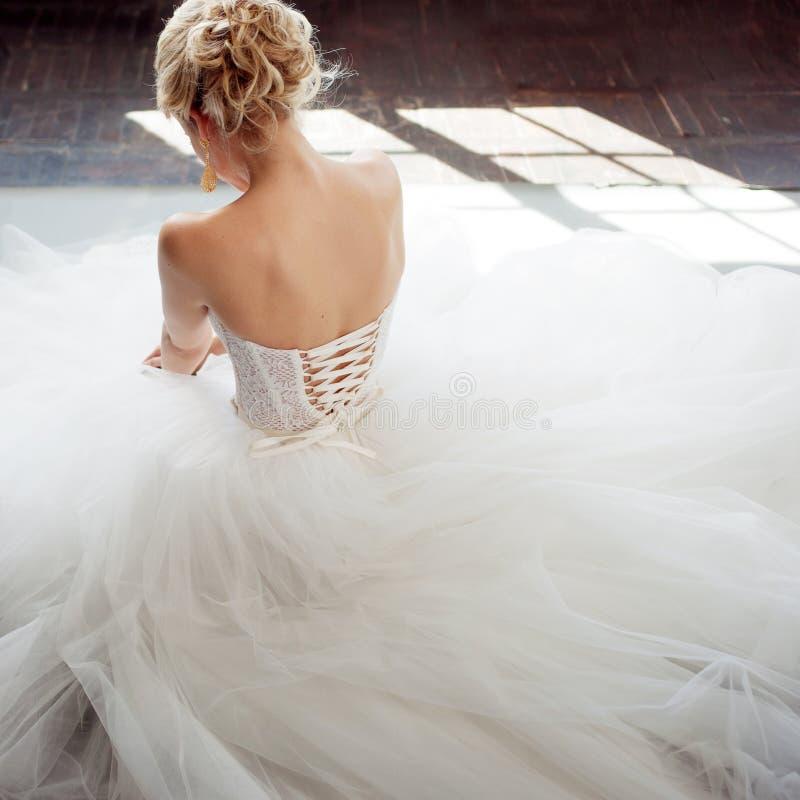 Noiva nova encantador no vestido de casamento luxuoso Menina bonita no branco Fundo cinzento back fotografia de stock royalty free