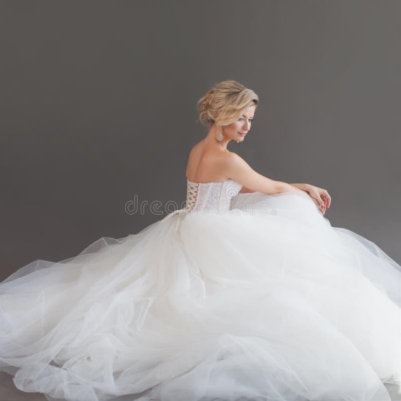 Noiva nova encantador no vestido de casamento luxuoso Menina bonita no branco Fundo cinzento back foto de stock