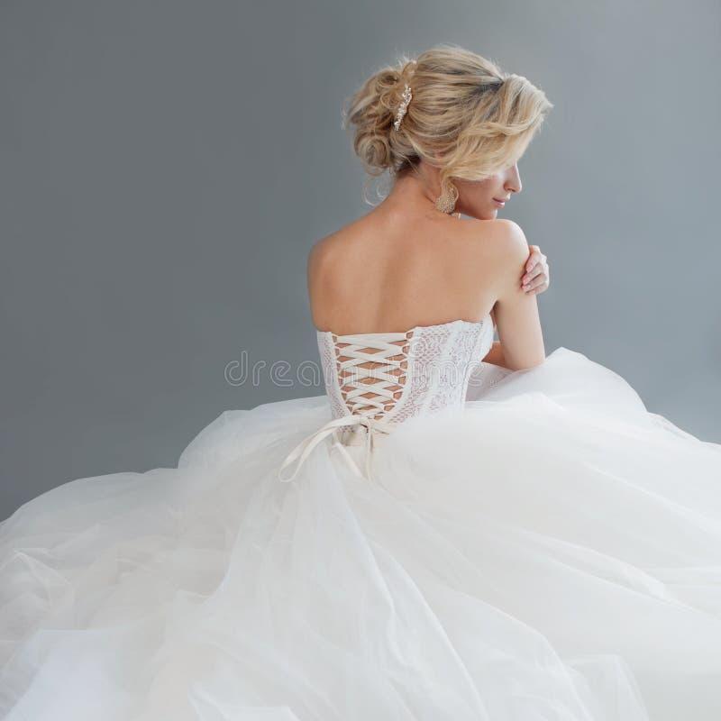 Noiva nova encantador no vestido de casamento luxuoso Menina bonita no branco Fundo cinzento back imagens de stock