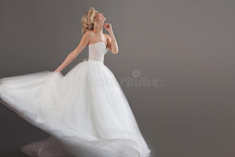 Noiva nova encantador no vestido de casamento luxuoso Menina bonita no fundo branco, cinzento, lugar para seu texto à direita imagens de stock royalty free