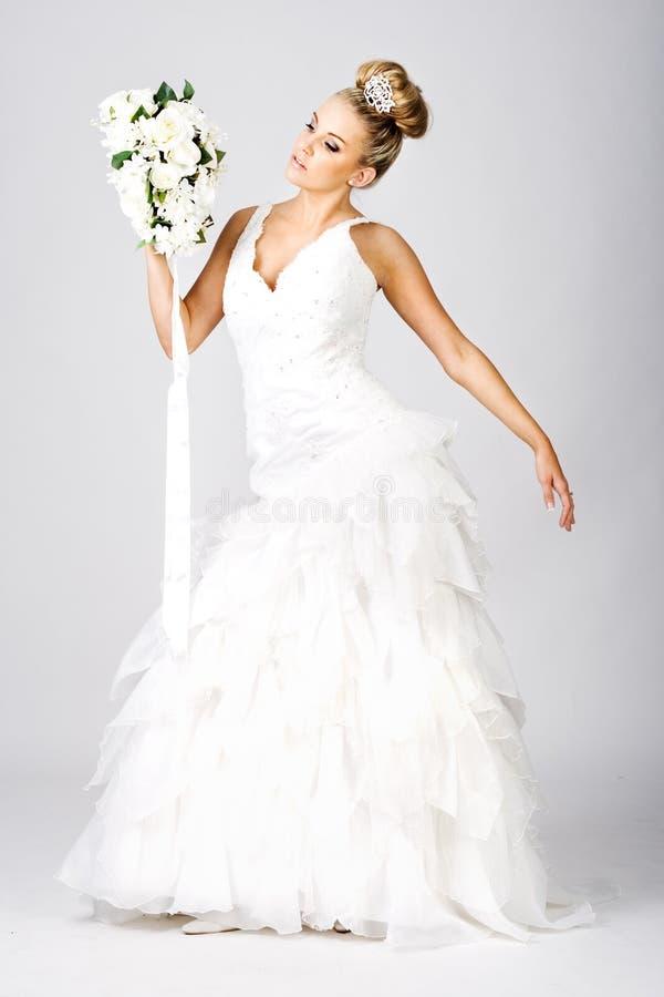 Noiva nova feliz com o ramalhete no branco fotografia de stock