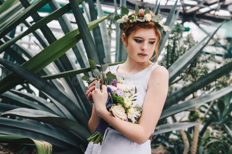 noiva nova macia bonita do ruivo que guarda o ramalhete do casamento em botânico foto de stock royalty free