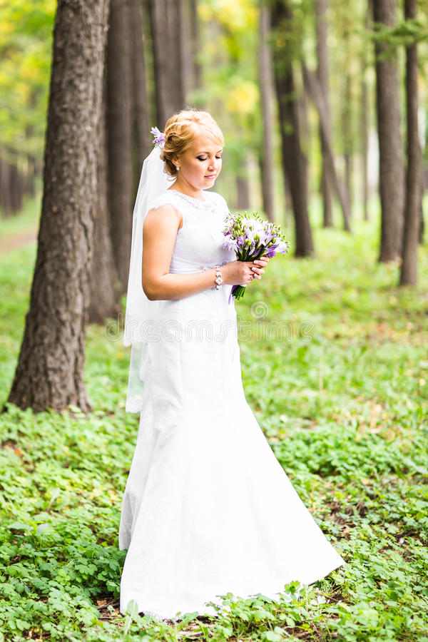 Noiva nova no vestido de casamento que guarda o ramalhete, fora fotos de stock royalty free